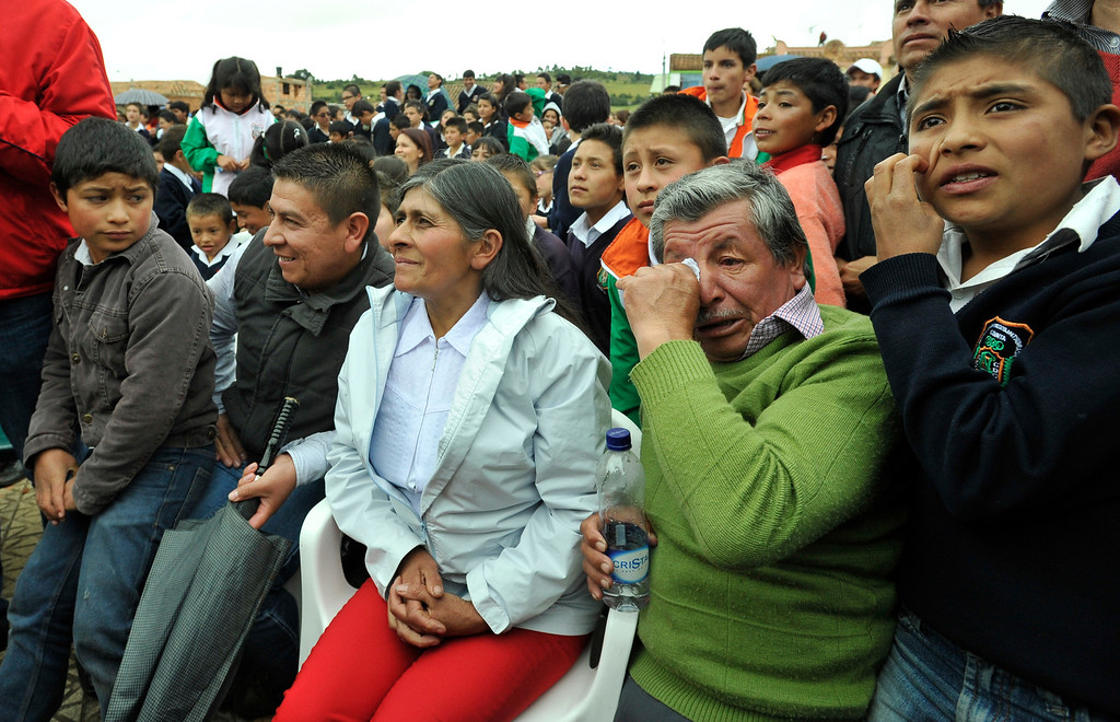 . Luis Quintana, second from right, and his wife Eloisa Rojas, third from right, parents of Movistar cyclist Nairo Quintana, watch their son compete in the 18th stage of the Tour de France cycling race at the main square of their hometown in Combita, central Colombia, Thursday, July 18, 2013. Relatives, resident and schoolchildren gathered at the main square of Quintana¥s hometown to follow his performance on a giant TV screen. (AP Photo/ Carlos Julio Martinez)