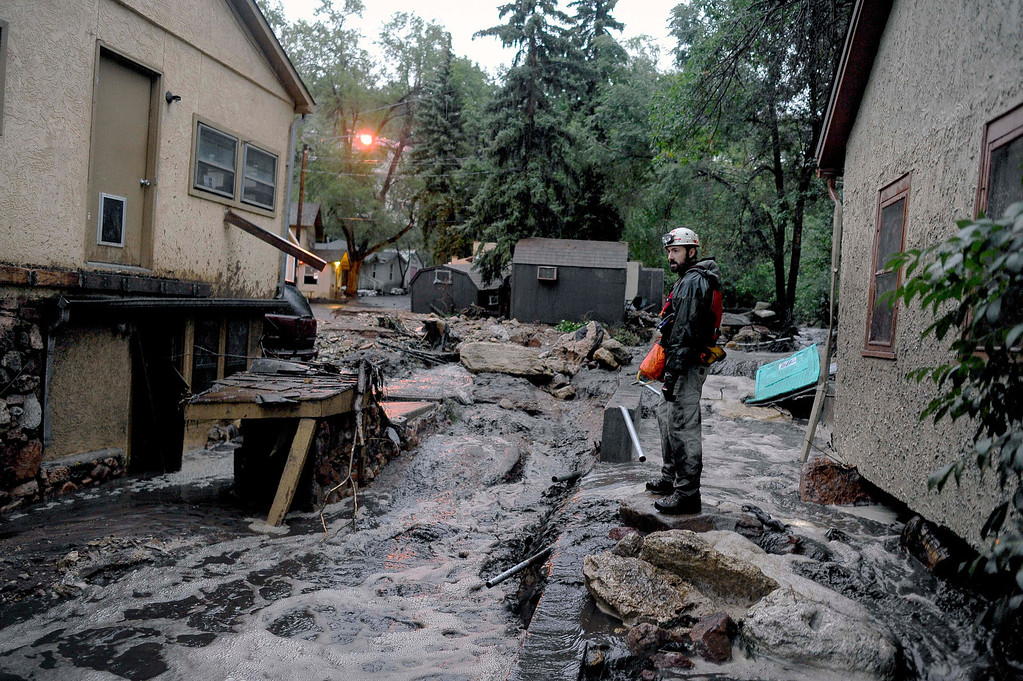 . Volunteer rescuer Jesse Rochette searches the Fountain Creek flood waters for anyone trapped or stranded as another flash flood washes off the Waldo Canyon burn scar, Friday, Aug. 9, 2013 in Manitou, Colo. A mudslide has closed U.S. 24 between Cascade and Manitou Springs, and flash flooding in Manitou Springs is stranding vehicles in high, fast-moving water. (AP Photo/The Colorado Springs Gazette, Michael Ciaglo)