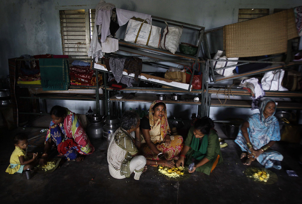 . Evacuated Indian villagers eat food in a temporary cyclone shelter in  Chatrapur , in Ganjam district about 200 kilometers  (125 miles) from the eastern Indian city Bhubaneswar, India, Saturday, Oct. 12, 2013. Strong winds and heavy rains pounded India\'s eastern coastline Saturday, as hundreds of thousands of people took shelter from a massive, powerful Cyclone Phailin expected to reach land in a few hours. (AP Photo/Biswaranjan Rout)