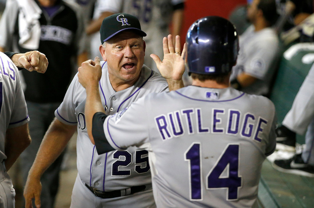 . Colorado Rockies\' hitting coach Blake Doyle gives a high five to Josh Rutledge after he scored in the third inning of a baseball game against the Arizona Diamondbacks, Saturday, Aug. 9, 2014, in Phoenix. (AP Photo/Darryl Webb)