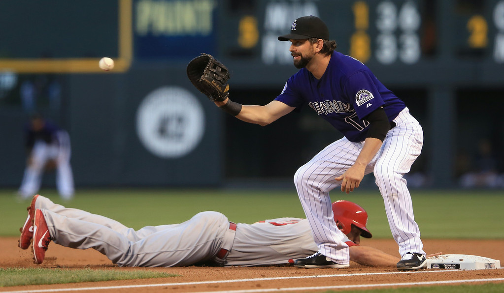 . First baseman Todd Helton #17 of the Colorado Rockies takes a pick off throw from pitcher Collin McHugh #43 of the Colorado Rockies to hold Matt Carpenter #13 of the St. Louis Cardinals on first base at Coors Field on September 16, 2013 in Denver, Colorado.  (Photo by Doug Pensinger/Getty Images)
