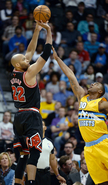 . Chicago Bulls power forward Taj Gibson (22) takes a shot over Denver Nuggets power forward Darrell Arthur (00) during the first quarter November 21, 2013 at Pepsi Center. (Photo by John Leyba/The Denver Post)