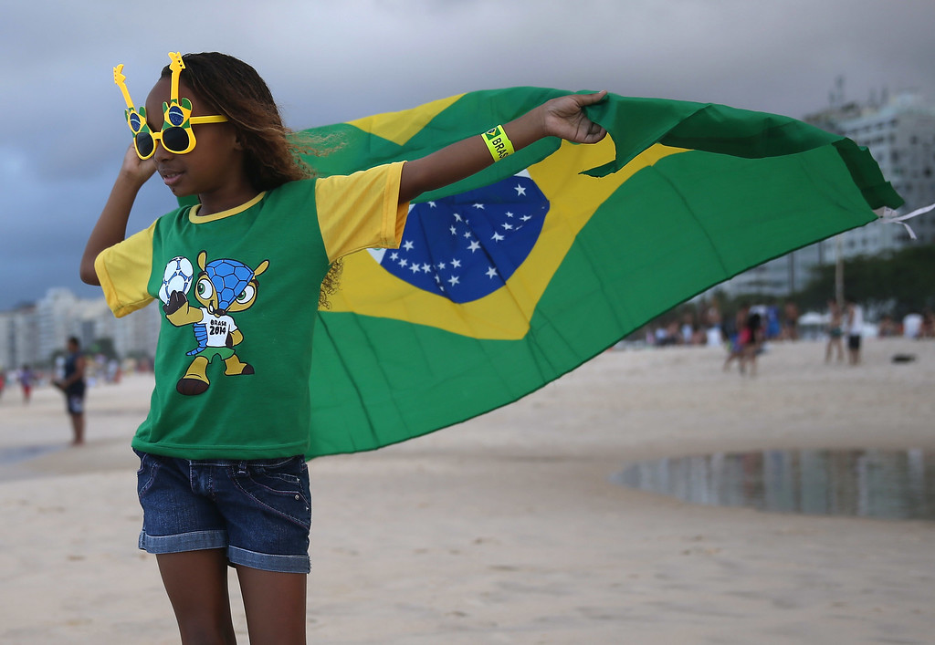 . Brazilian soccer team fan, Giovanna Selena, from Brazil, flies her countries flag as she enjoys Copacabana beach while waiting for the start of the 2014 FIFA World Cup on June 11, 2014 in Rio de Janeiro, Brazil.   Brazil continues to prepare to host the World Cup which starts on June 12th and runs through July 13th.  (Photo by Joe Raedle/Getty Images)