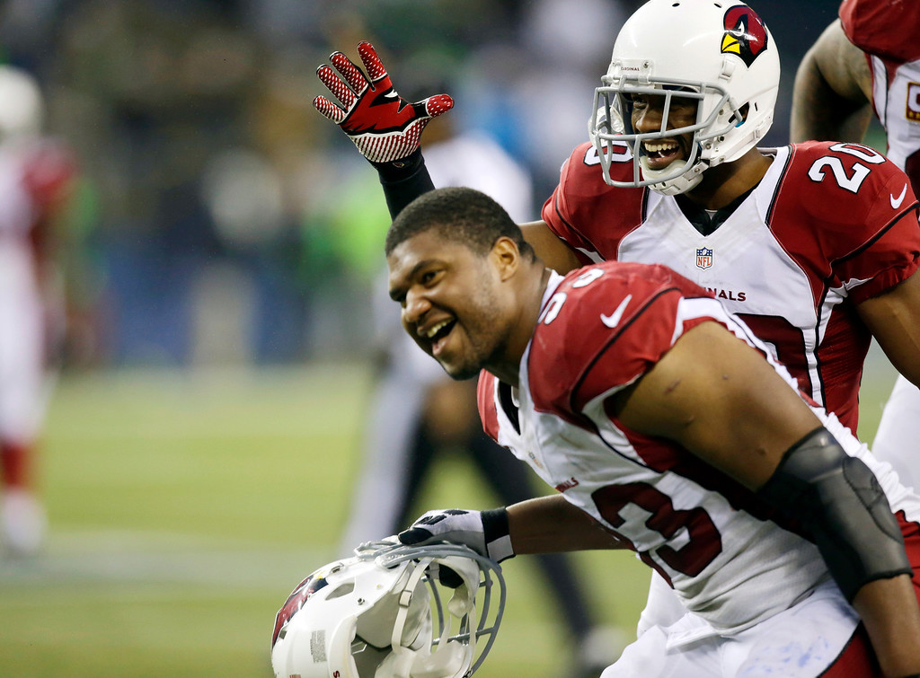 . Arizona Cardinals\' Antoine Cason, right, and Calais Campbell, left, celebrate after Cardinals\' Karlos Dansby made an interception in the second half of an NFL football game against the Seattle Seahawks, Sunday, Dec. 22, 2013, in Seattle. The Cardinals won 17-10. (AP Photo/Stephen Brashear)