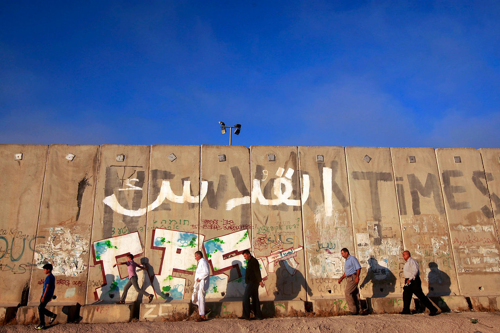 . Palestinians men walk towards an Israeli checkpoint on their way to pray at the Al-Aqsa Mosque in Jerusalem during the Muslim holy month of Ramadan at the Qalandia checkpoint between the West Bank city of Ramallah and Jerusalem, Friday, July 26, 2013. (AP Photo/Majdi Mohammed)