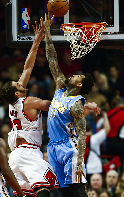 . Denver Nuggets forward Wilson Chandler (R) tries to block a shot by Chicago Bulls center Joakim Noah (L) in the first half of their NBA game at the United Center in Chicago, Illinois, USA, 21 February 2014  EPA/TANNEN MAURY