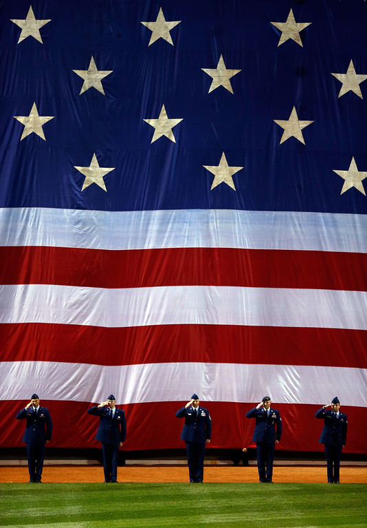 . Servicemen salute during the national anthem before Game One of the 2013 World Series between the Boston Red Sox and the St. Louis Cardinals at Fenway Park on October 23, 2013 in Boston, Massachusetts.  (Photo by Jared Wickerham/Getty Images)