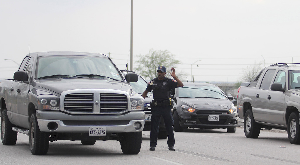 . Emergency personnel caution drivers away from the Bernie Beck Main Gate following reports of a shooting, Wednesday, April 2, 2014 at Fort Hood, Texas. (AP Photo/Killeen Daily Herald, Catrina Rawson)