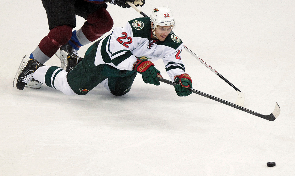 . Minnesota Wild\'s Nino Niederreiter (22), of Switzerland, reaches for the puck during the first period of an NHL hockey game against the Colorado Avalanche on Thursday, Jan. 30, 2014, in Denver. (AP Photo/Barry Gutierrez)