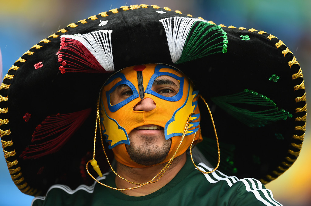 . A Mexico fan looks on through the rain prior to the 2014 FIFA World Cup Brazil Group A match between Mexico and Cameroon at Estadio das Dunas on June 13, 2014 in Natal, Brazil.  (Photo by Matthias Hangst/Getty Images)
