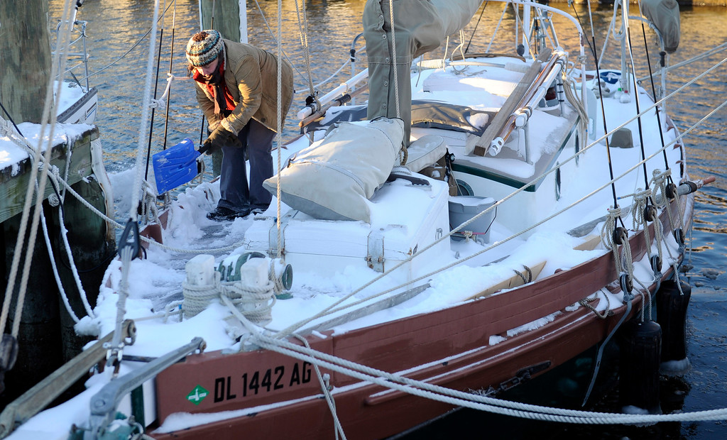 . Erin Maloney of Annapolis, Md., clears snow off of her boat docked  at the Annapolis City Dock, Wednesday, Jan. 22, 2014. Residents along the Mid-Atlantic are digging out after a massive winter storm packing up to a foot of snow, strong winds and icy temperatures slammed into the region. (AP Photo/Susan Walsh)