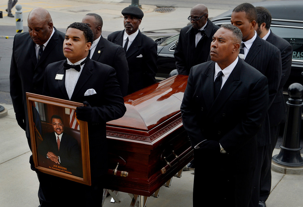 . Brandon Dorsey holds a portrait of former Lt. Gov. Joe Rogers as pallbearers prepare to carry the casket into the state Capitol in Denver, CO October 15, 2013.  (Photo By Craig F. Walker / The Denver Post)