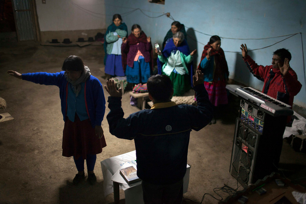 . Villagers pray at the end of the day during an evangelical service, after attending a mass burial of other villagers slain by insurgents nearly three decades ago, in Chaca , Peru. A Truth and Reconciliation Commission estimated that Peru\'s 1980-2000 conflict claimed nearly 70,000 lives, most of them poor, Quechua-speaking people. Some 15,000 of them disappeared. Yet fewer than 3,000 bodies have been exhumed because the country has lagged in healing the wounds of its war. (AP Photo/Rodrigo Abd)