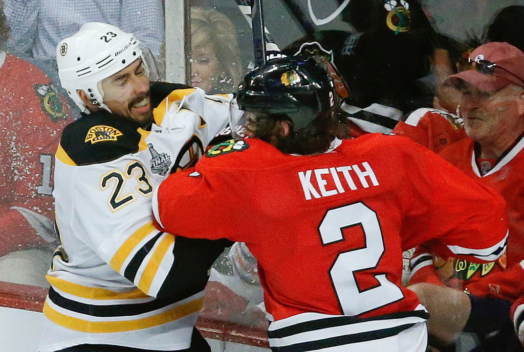 . Boston Bruins center Chris Kelly (23) collides with Chicago Blackhawks defenseman Duncan Keith (2) in the third period during Game 5 of the NHL hockey Stanley Cup Finals, Saturday, June 22, 2013, in Chicago. (AP Photo/Charles Rex Arbogast)