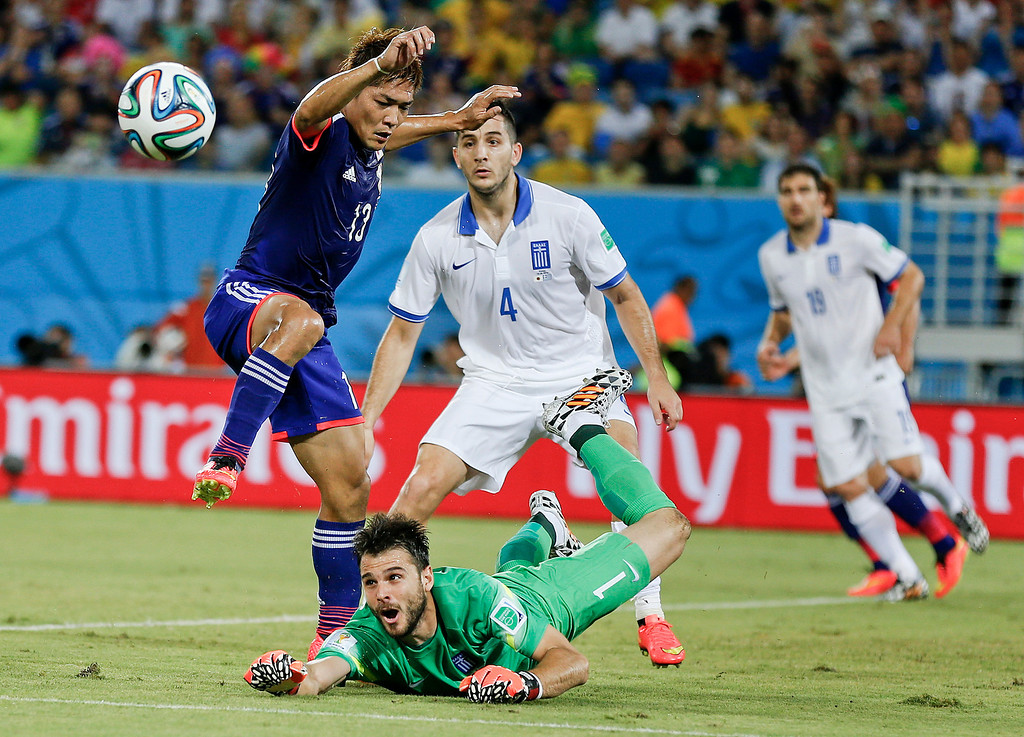 . Greece\'s goalkeeper Orestis Karnezis makes a save at the feet of Japan\'s Yoshito Okubo during the group C World Cup soccer match between Japan and Greece at the Arena das Dunas in Natal, Brazil, Thursday, June 19, 2014.  (AP Photo/Frank Augstein)