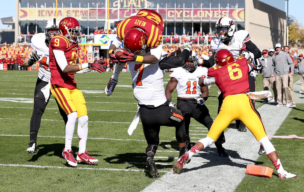. Iowa State running back DeVondrick Nealy (20) jumps over the top of Oklahoma State safety Shamiel Gary (7) to score a touchdown during the first half of an NCAA college football game in Ames, Iowa Saturday, Oct. 26, 2013.(AP Photo by Justin Hayworth)