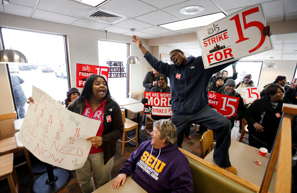. Protesters rally for better wages inside a Wendy\'s restaurant in Detroit Thursday, Dec. 5, 2013. (AP Photo/Paul Sancya)