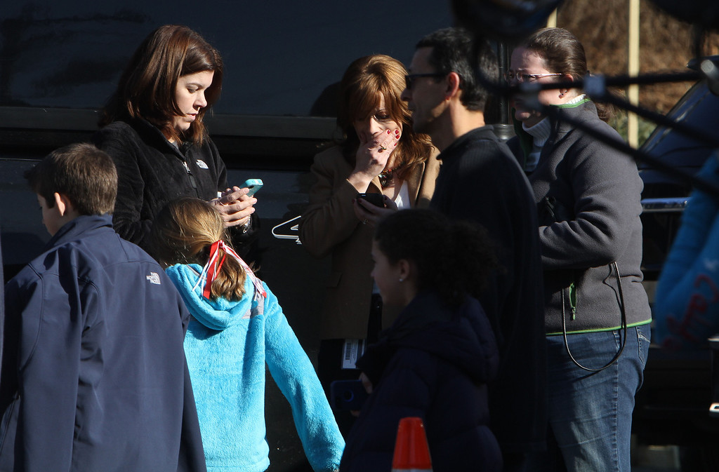 . A woman weeps as she arrives to pick up her children at the Sandy Hook Elementary School, Friday, Dec. 14, 2012 in Newtown, Conn. A man opened fire inside the Connecticut elementary school where his mother worked Friday, killing 26 people, including 18 children, and forcing students to cower in classrooms and then flee with the help of teachers and police. (AP Photo/The Journal News, Frank Becerra Jr.)
