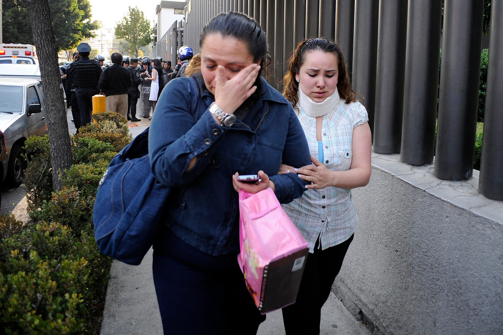 . Two women react while leaving the premises of state oil giant Pemex in Mexico City January 31, 2013. A powerful explosion rocked the Mexico City headquarters of state oil giant Pemex on Thursday, killing at least 14 people and injuring 100 others.The blast hit the lower floors of the downtown tower block, throwing debris into the streets and sending workers running outside. Interior Minister Miguel. REUTERS/Alejandro Dias