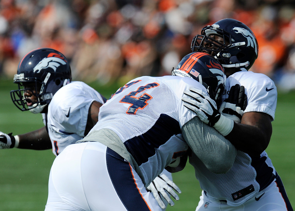 . ENGLEWOOD, CO - JULY 27: Denver Broncos offensive linemen, Vinston Painter, right, and Orlando Franklin, center,  battle training at Dove Valley Saturday July 26, 2013.  (Photo By Andy Cross/The Denver Post)