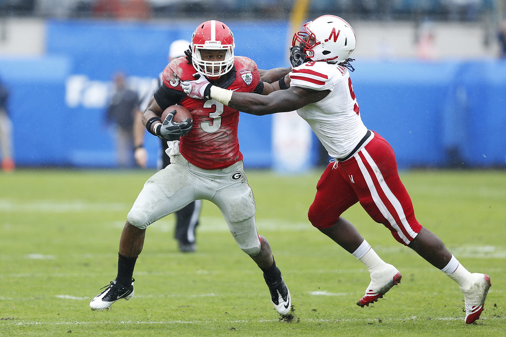 . Todd Gurley #3 of the Georgia Bulldogs runs the ball in the first half against Jason Ankrah #9 of the Nebraska Cornhuskers during the TaxSlayer.com Gator Bowl at Everbank Field on January 1, 2014 in Jacksonville, Florida. (Photo by Joe Robbins/Getty Images)
