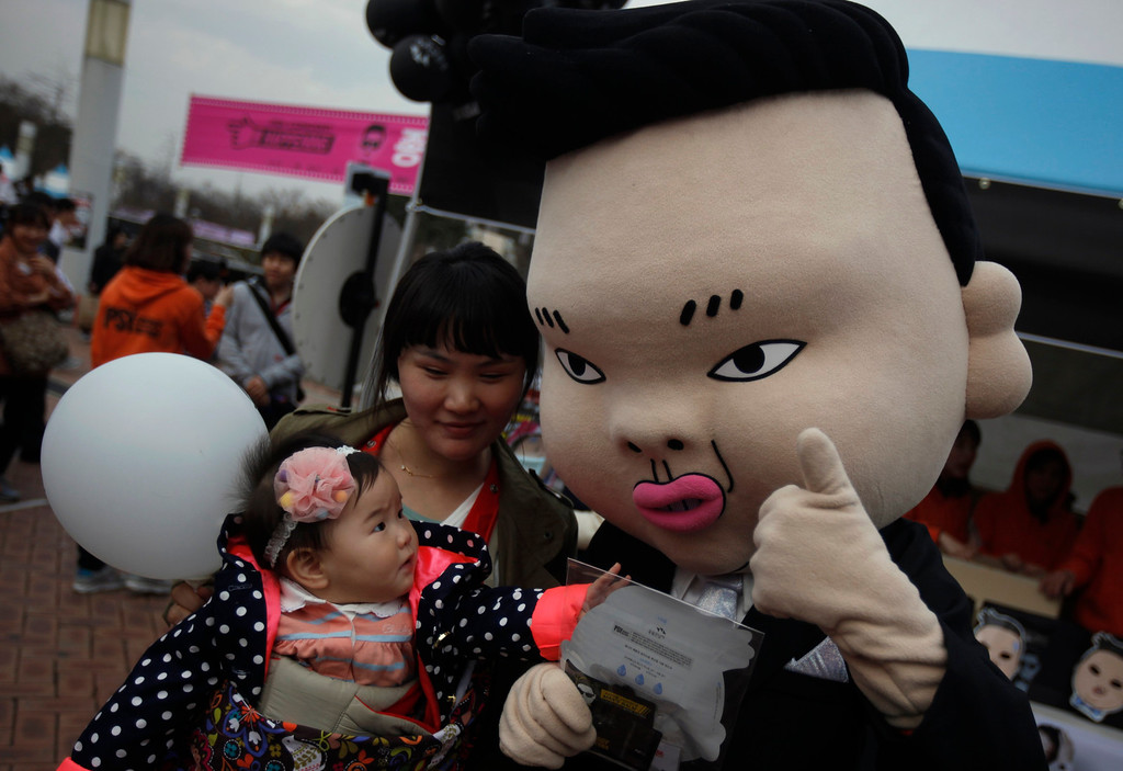 ". A baby looks at a mask of South Korean rapper Psy at the Seoul World Cup stadium, where is venue for the Psy\'s concert ""happening\"" in Seoul April 13, 2013. Psy will perform \""Gentleman\"" in public for the first time on Saturday at a concert at Seoul\'s World Cup stadium but he has been coy about what dance to expect this time, except to hint that it is based on traditional Korean moves. Psy released his new single on Thursday hoping to repeat the success of \""Gangnam Style\"" that made him the biggest star to emerge from the growing K-pop music scene.   REUTERS/Kim Hong-Ji"