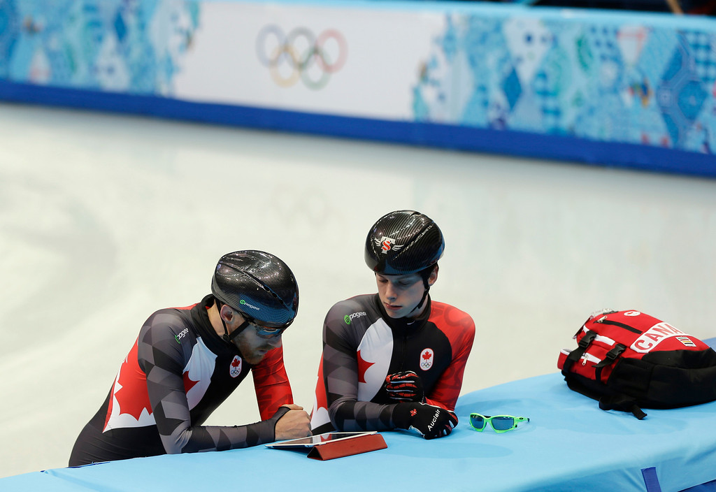 . Canada\'s Jean Olivier, left, and Charle Cournoyer look at a tablet device during a team short track speed skating training session at the Iceberg Skating Palace ahead of the 2014 Winter Olympics, Tuesday, Feb. 4, 2014, in Sochi, Russia. (AP Photo/Mark Baker)
