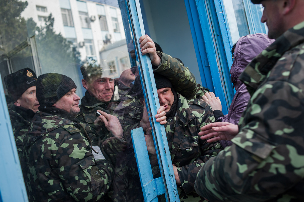 . Pro-Russian self-defense force members get through an entrance to the Ukrainian Navy headquarters in Sevastopol, Crimea, Wednesday, March 19, 2014. An Associated Press photographer said several hundred militiamen took down the gate and made their way onto the base. They then raised the Russian flag in the square by the headquarters. The unarmed militia waited for an hour on the square before the move to storm the headquarters. Following the arrival of the commander of the Russian Black Sea fleet, the Crimeans took over the building. (AP Photo/Andrew Lubimov)