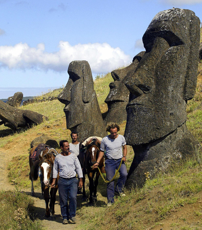 . Captain Patrice Franceschi (L), topman Bruno Tomasi (C), and lieutenant Pierre Marcel, of the exploration and research ship La Boudeuse, lead their horses along the hillside of the Rano Raraku volcano during an excursion across Easter Island, off the coast of Chile, 07 February 2005. The three-masted schooner undertakes the second of twelve sailing expeditions around the world with the aim of re-discovering the people of the water.  MARTIN BERNETTI/AFP/Getty Images