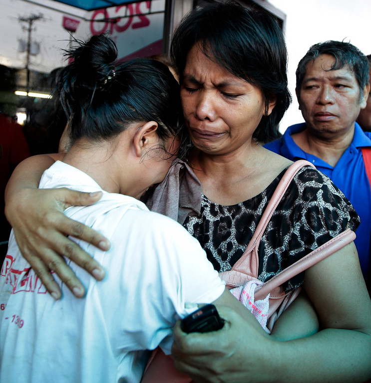 . A survivor, left, of the ill-fated passenger ferry MV Thomas Aquinas, is comforted by a relative outside the ticketing office of a shipping company, Saturday Aug. 17, 2013, a day after the ferry collided with a cargo ship, the MV Sulpicio Express Siete, off the waters of Talisay city, Cebu province in central Philippines. Divers combed through the sunken ferry Saturday in search of dozens of people missing after the collision that sent passengers jumping into the ocean and leaving many others trapped. At least 31 were confirmed dead and hundreds rescued. (AP Photo/Bullit Marquez)