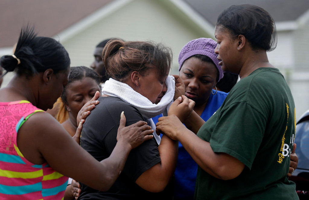 . Lisa North, the mother of missing 6-year-old Ahlittia North, is comforted by her mother, Rene\' Johnson, right, and others, after she says Jefferson Parish authorities have found the body of her daughter in a Harvey trash bin, in Harvey, La., Tuesday, July 16, 2013. Ahlittia disappeared from her apartment late Friday night or early Saturday morning. North\'s husband Albert Hill said they were told the body was found in a trash bin not far from their apartment. (AP Photo/Gerald Herbert)
