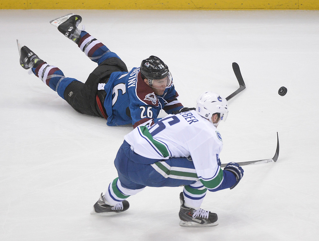 . DENVER, CO - MARCH 27: Colorado center Paul Stastny (26) tried to clear the puck away from Vancouver defenseman Yannick Weber (6) in the second period. The Colorado Avalanche hosted the Vancouver Canucks Thursday night, March 27, 2014 at the Pepsi Center in Denver, Colorado. (Photo by Karl Gehring/The Denver Post)