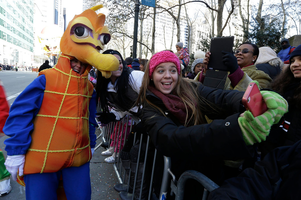 . Kayla Mieczkowski, 17, right, of Holbrook, N.Y., takes a photograph of herself with a performer during the Macy\'s Thanksgiving Day Parade, Thursday, Nov. 28, 2013, in New York. (AP Photo/Julio Cortez)