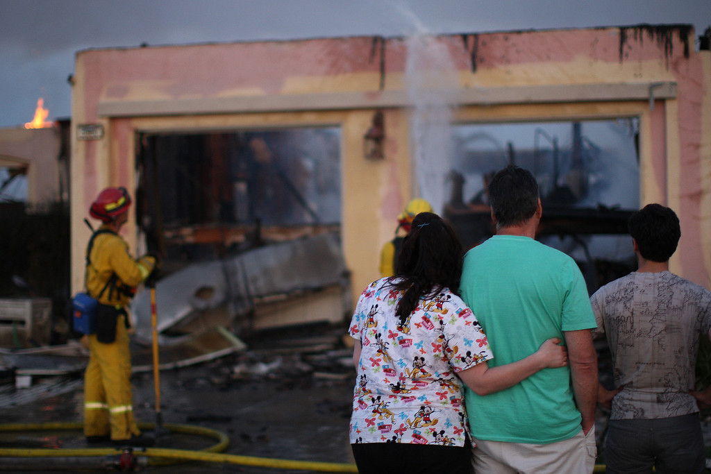 . Residents looks at the burning remains of their home that was destroyed in the Poinsettia fire, one of nine wildfires fueled by wind and record temperatures that erupted in San Diego County throughout the day, on May 14, 2014 in Carlsbad, California.  (Photo by David McNew/Getty Images)
