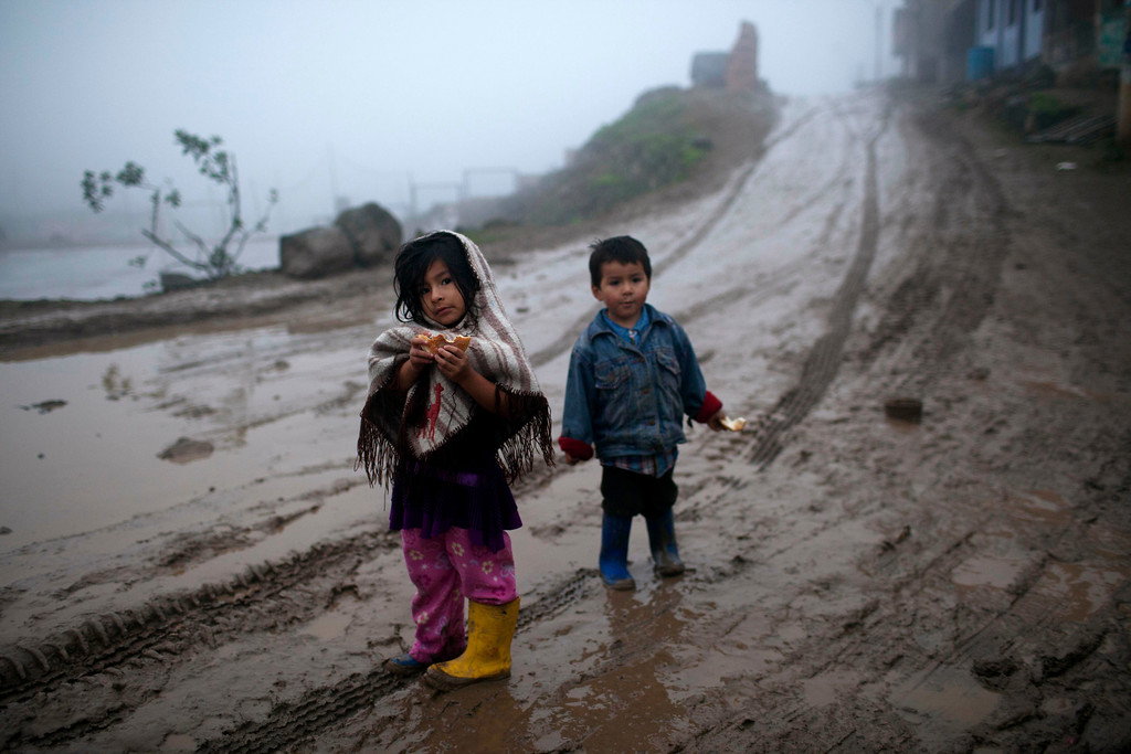 . In this Aug. 4, 2013 photo, children stand at a muddy road during an intense drizzle in Lima, Peru. For roughly four months a year, the sun abandons Peru\'s seaside desert capital, suffocating it under a ponderous gray cloudbank and fog that coats the city with nighttime drizzles. Limenos don scarfs and jackets and complain of slipping into a gloom of seasonal depression. (AP Photo/Rodrigo Abd)
