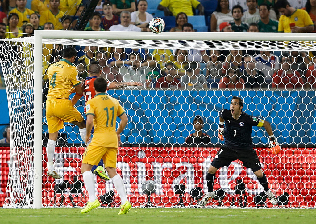 . Chile\'s goalkeeper Claudio Bravo (1) watches as Australia\'s Tim Cahill (4) heads the ball to score his side\'s first goal during the first half of the group B World Cup soccer match between Chile and Australia in the Arena Pantanal in Cuiaba, Brazil, Friday, June 13, 2014.   (AP Photo/Kirsty Wigglesworth)