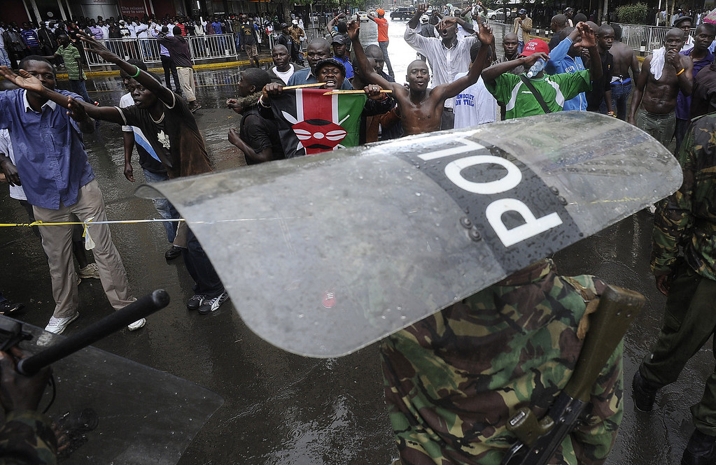 . A Kenyan police officer holds a shield as he keeps vigil outside the Supreme Court in Nairobi on March 30, 2013 as a supporter of Prime Minister Raila Odinga urges with policemen. Kenya\'s Supreme Court on Saturday upheld the election of Uhuru Kenyatta as the country\'s next president, ending an election season that riveted the nation amid fears of a repeat of the 2007-08 postelection violence. SIMON MAINA/AFP/Getty Images