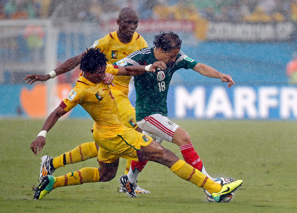 . Mexico\'s Andres Guardado, right, is challenged by Cameroon\'s Jean Makoun during the group A World Cup soccer match between Mexico and Cameroon in the Arena das Dunas in Natal, Brazil, Friday, June 13, 2014.  (AP Photo/Sergei Grits)