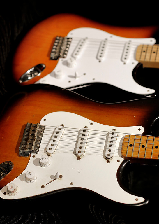 ". An original 1954 Fender Stratocaster, foreground, is shown next to a 2014 model at a studio in Scottsdale, Ariz. on Friday, Jan. 10, 2014. The Stratocaster has a unique voice that differs from other electric guitars due to its 3 pickups and has been described as ""glassy,\"" \""bright\"" or \""clean.\"" (AP Photo/Matt York)"