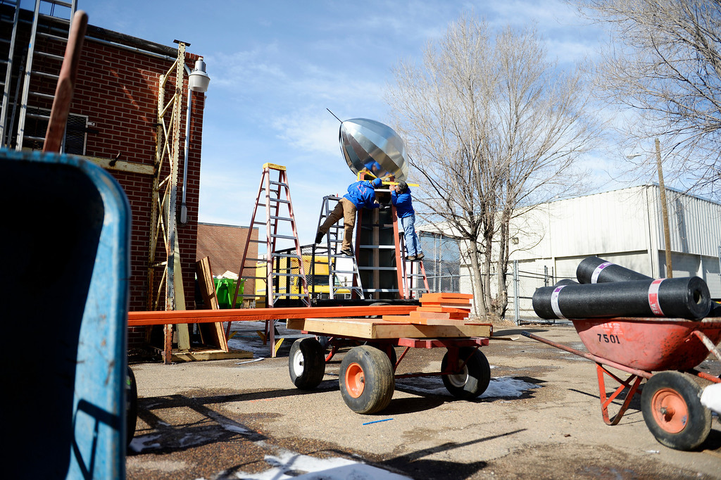 . John Darling, left, Carlos Tovar, both employees at Frontier Roofing System in east Denver, work on making a 14-foot Vince Lombardi Trophy, January, 26 2014.  (Photo by RJ Sangosti/The Denver Post)