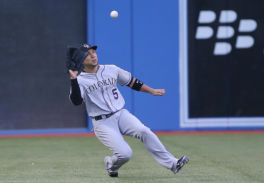 . Carlos Gonzalez #5 of the Colorado Rockies makes a sliding catch in the first inning during MLB game action against the Toronto Blue Jays on June 19, 2013 at Rogers Centre in Toronto, Ontario, Canada. (Photo by Tom Szczerbowski/Getty Images)