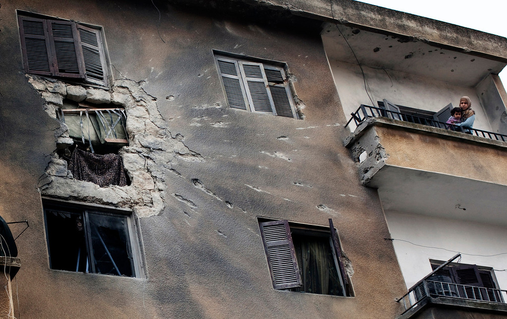 . FILE - A woman holds her daughter on the balcony of her building damaged by Syrian Army bombings in central  Idlib, north of Syria, Monday, Feb. 27, 2012. (AP Photo/Rodrigo Abd, File)