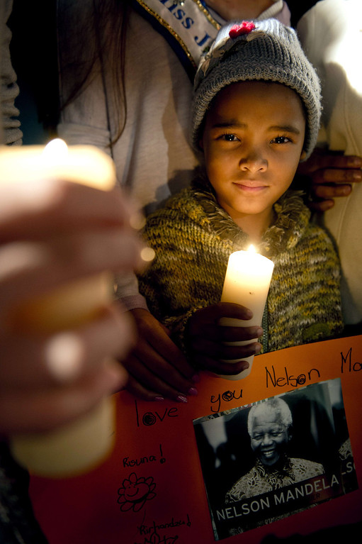 . A boy holds a picture of Nelson Mandela during a candle lit vigil outside the Mediclinic Heart Hospital in Pretoria where a community group prayed and sang religious songs in support of Mandela who is receiving treatment there, on June 25, 2013. Mandela\'s close family gathered today at his rural homestead to discuss the failing health of the South African anti-apartheid icon who was fighting for his life in hospital. Messages of support poured in from around the world for the Nobel Peace Prize winner, who spent 27 years behind bars for his struggle under white minority rule and went on to become South Africa\'s first black president. ODD ANDERSEN/AFP/Getty Images