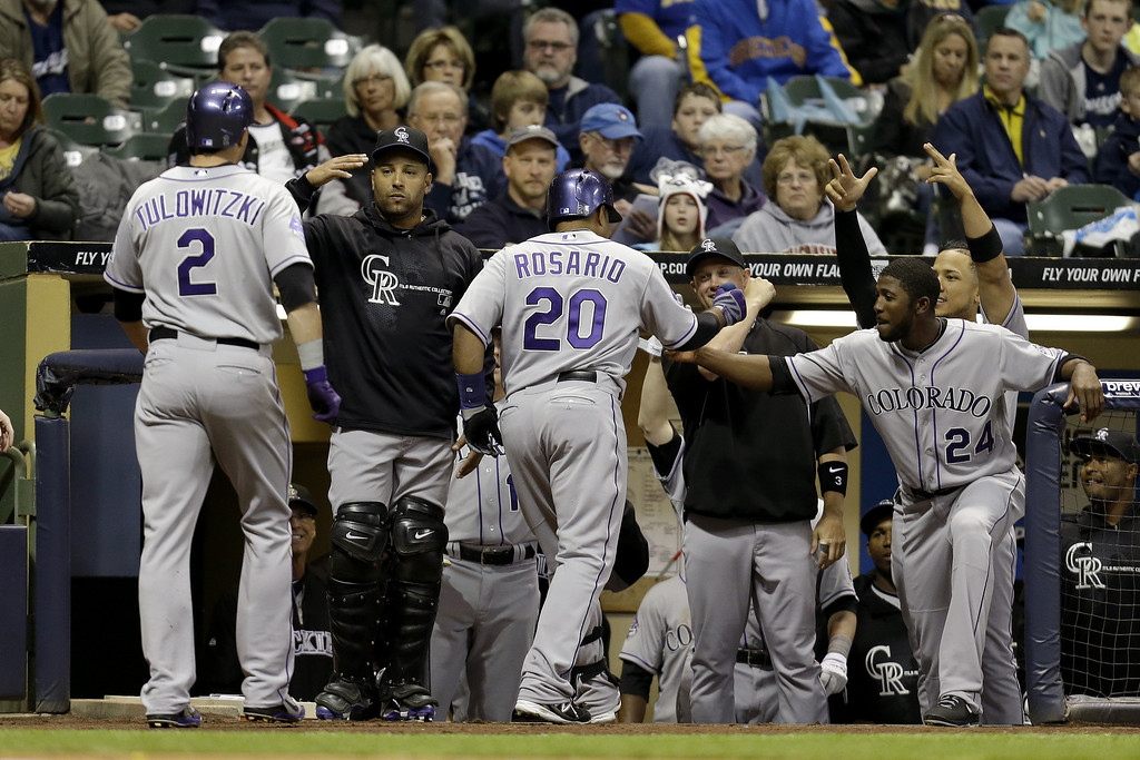 . MILWAUKEE, WI - APRIL 3:  Wilin Rosario #20 of the Colorado Rockies celebrates outside the dugout after hitting a two-run homer in the top of the second inning scoring Troy Tulowitzki #2 against the Milwaukee Brewers at Miller Park on April 3, 2013 in Milwaukee, Wisconsin. (Photo by Mike McGinnis/Getty Images)