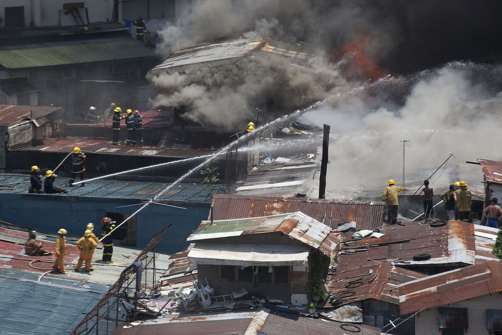 . Firemen on top of corrugated rooves extinguish a fire that engulfed a shanty town in the financial district of Manila on July 11, 2013. There were no immediate reports of casualties from the blaze, which occurred mid-morning amid government plans to relocate thousands of families living in areas vulnerable to floods and typhoons. KARL MALAKUNAS/AFP/Getty Images