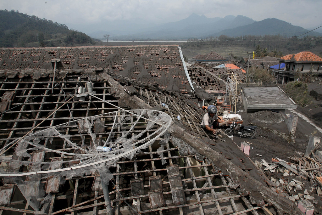 . A man repairs a roof his house following an eruption of Mount Kelud, in Malang, East Java, Indonesia, Monday, Feb. 17, 2014.  (AP Photo/Trisnadi)