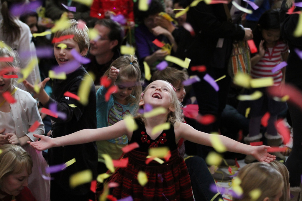 . Cora Murphy-Usher, 7, of Narberth, Pa. is totally captivated by the streaming confetti coming down from the sky inside the Please Touch Museum as she and hundreds more, celebrated the New Year at noon on Tuesday , Dec. 31, 2013 in Philadelphia.  (AP Photo/The Philadelphia Inquirer, Michael Bryant)