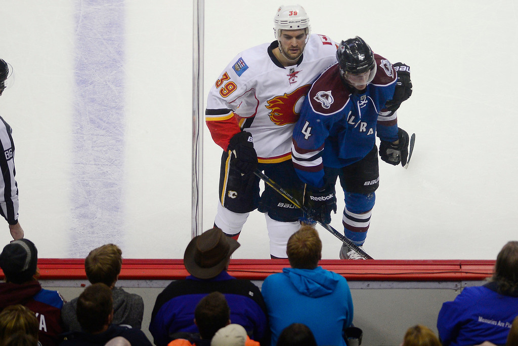 . T.J. Galiardi (39) of the Calgary Flames puts his arm around Tyson Barrie (4) of the Colorado Avalanche as the action breaks during the second period.  (Photo by AAron Ontiveroz/The Denver Post)