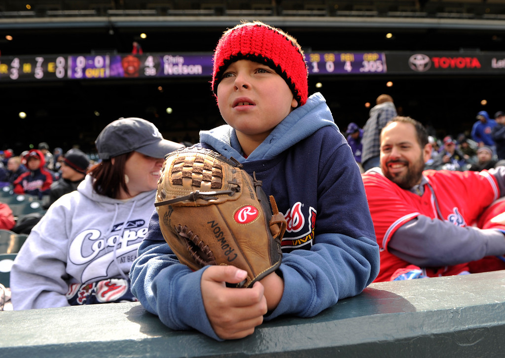 . DENVER, CO. - APRIL 23:  Cooper Crowson, age 7, attended the game with his parents Alisha, left, and Tony, right, Tuesday afternoon. The Braves fans came down from Fish Haven, Montana too see the game. The Atlanta Braves defeated the Colorado Rockies 4-3 at Coors Field Tuesday, April 23, 2013.  The first game of the doubleheader Tuesday was a make-up from Monday night\'s postponement due to weather.  Photo By Karl Gehring/The Denver Post
