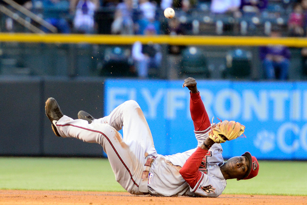 . DENVER, CO - MAY 21: Didi Gregorius (1) of the Arizona Diamondbacks attempts a circus throw, btu was unable to get an out on Jhoulys Chacin (45) of the Colorado Rockies during action at Coors Field. The Arizona Diamondbacks visited the Colorado Rockies. (Photo by AAron Ontiveroz/The Denver Post)
